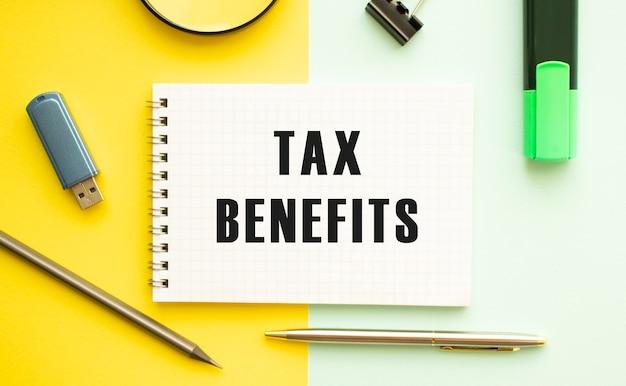 Notitieboekje met tekst belastingvoordelen op kantoortafel met kantoorbenodigdheden