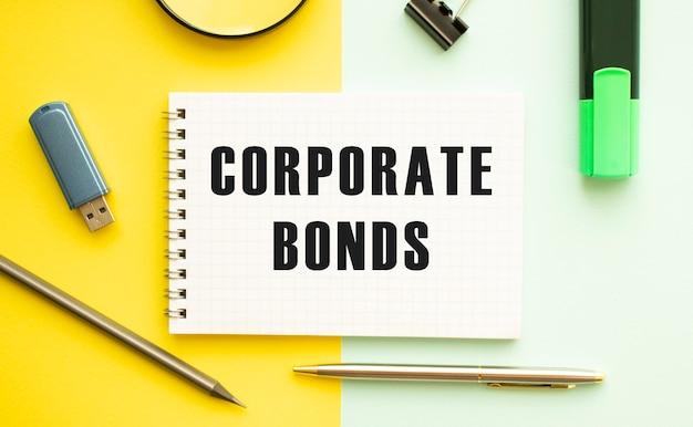 Notitieboekje met tekst corporate bonds op kantoortafel met kantoorbenodigdheden. gele kleur oppervlakte concept.