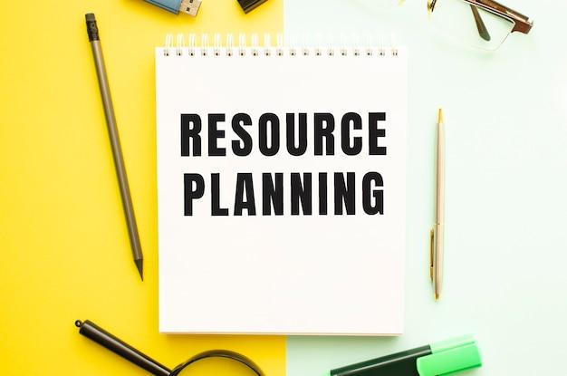 Notitieboekje met tekst resource planning op kantoortafel met kantoorbenodigdheden. gele kleur achtergrond concept.