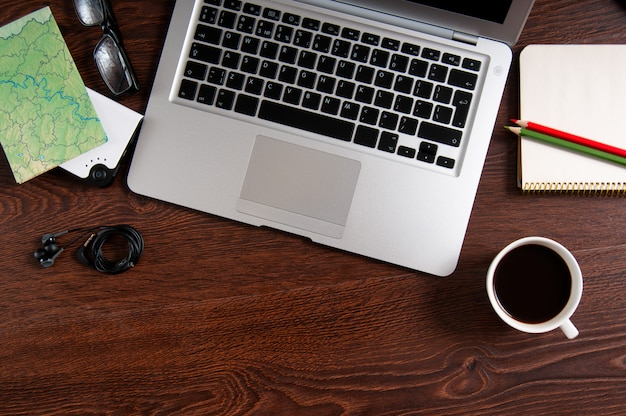 Notitieboekje met warme koffie en kaart op houten tafel