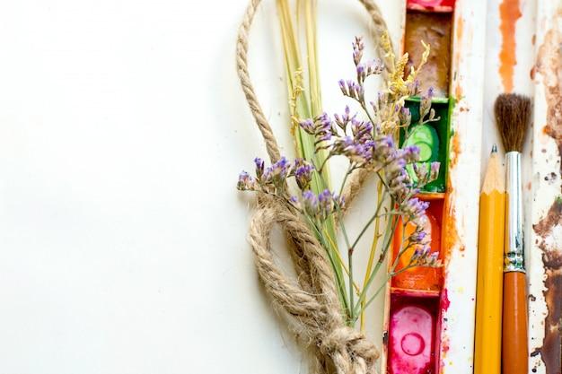 Notitieboekje met waterverfverven, bloemen en een potlood