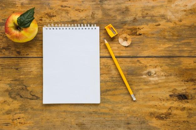 Notitieboekje met whittled het schrijven potlood en appel dichtbij