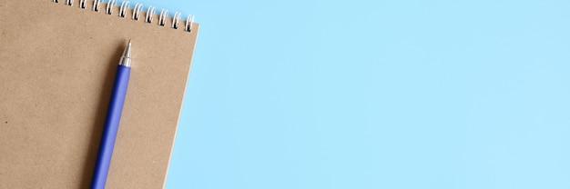 Notitieboekje of schetsboek gemaakt van kraftpapier en een pen op een blauwe achtergrond. ruimte voor tekst. banner