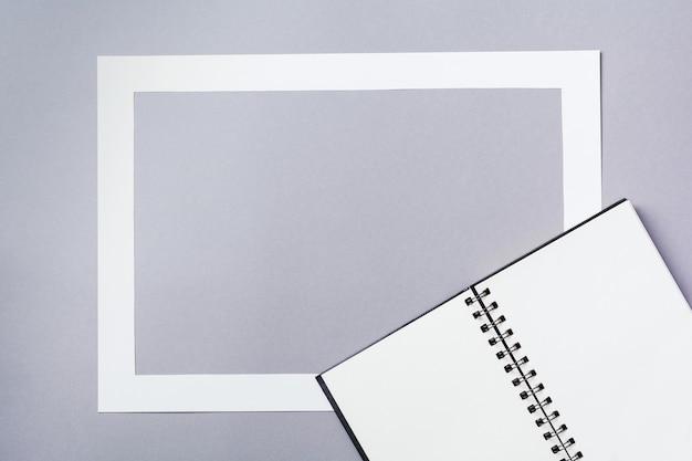 Notitieboekje of schetsboek met papieren kaartframe op klassieke grijze achtergrond met het effect van vallende sneeuw