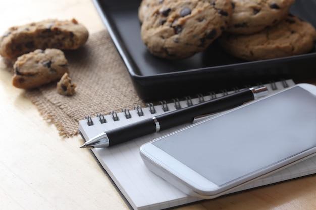 Notitieboekje op bureau met koffiekoekje en pen