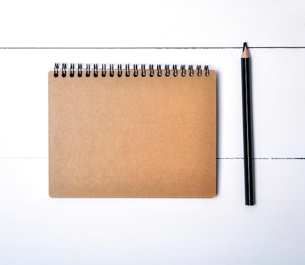 Notitieboekje op de zwarte ijzerlente met bruine lege bladen