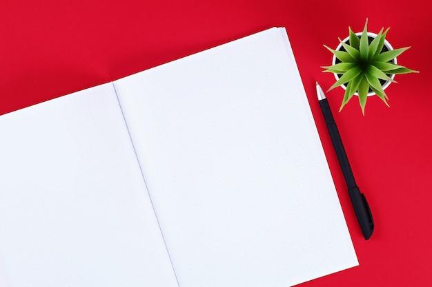 Notitieboekje op een rode achtergrond.