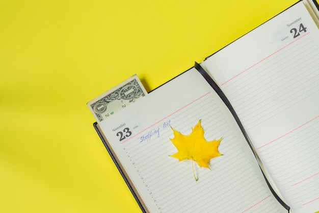 Notitieboekje op geel. boodschappenlijstje op black friday en een bladwijzer van één dollar.