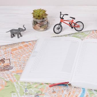 Notitieboekje op kaart dichtbij stuk speelgoed dier en fiets