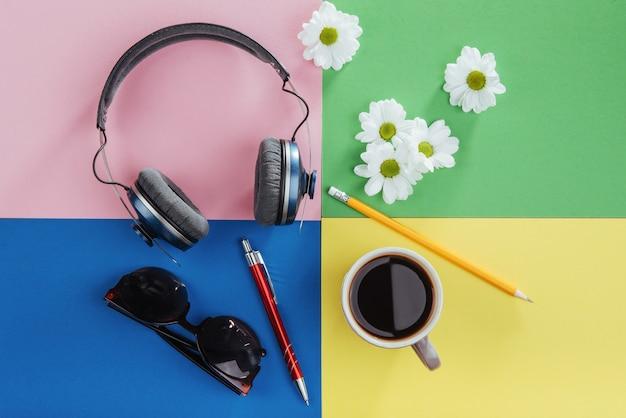Notitieboekje, potlood, glazen, koffie en geurige witte bloemen.
