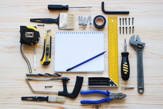 Notitieboekje voor verslagen en bouwhulpmiddelen om een huis of flatvernieuwing, op een houten lijst te bouwen. de werkplaats van de voorman. het thema van thuis en professionele reparatie, bouw.