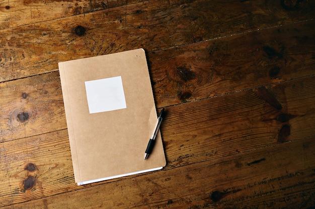Notitieboekje zonder label en een plastic zwarte pen op een oude getextureerde houten tafel