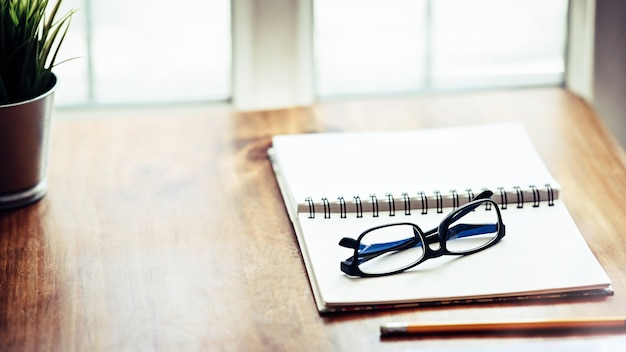 Notitieboekjedocument glazen op houten lijst openen.