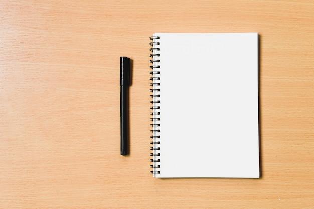 Notitieboekjedocument met blanco pagina voor copyspace en blakcpen voor notabericht op houten lijst