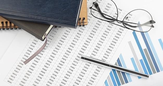 Notitieboekjes en bedrijfsgrafiek met pen en glassses, concept