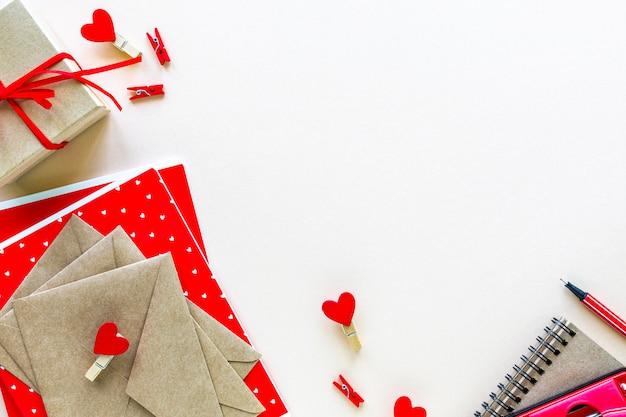 Notitieboekjes en enveloppen voor school of kantoor in het rood op een witte tafel met kopie ruimte.