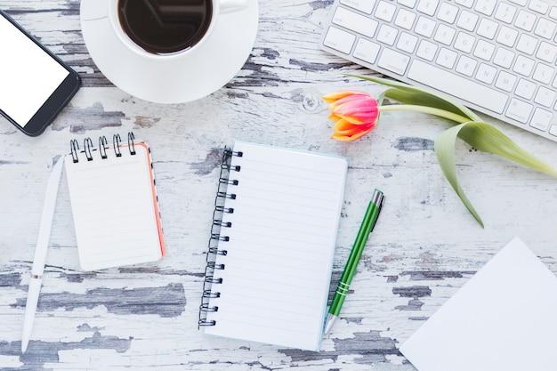 Notitieboekjes en koffiekopje dichtbij smartphone en toetsenbord op bureau met tulpenbloem