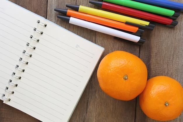 Notitieboekjes en mandarijn sinaasappelen