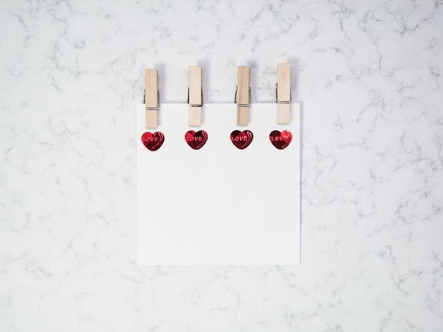 Notitiepapier met houten wasknijper en hartvorm op marmeren achtergrond, gelukkige valentijnsdag, moederdag, plat leggen, bovenaanzicht