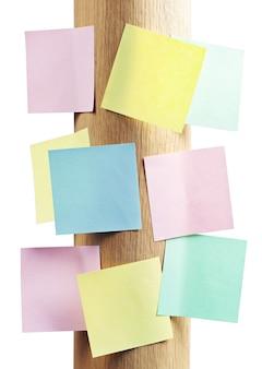 Notitiepapier van verschillende kleuren op een op een ronde, houten standaard geïsoleerd op wit