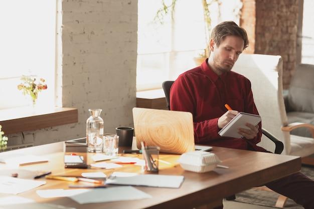 Notities maken. kaukasische ondernemer, zakenman, manager die op kantoor probeert te werken.