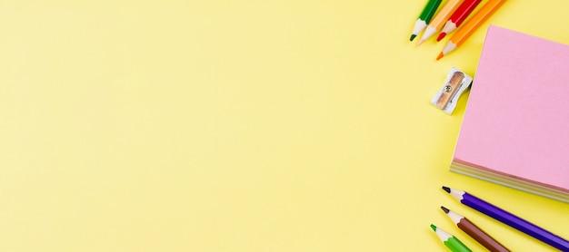 Notities met potloden op een gele achtergrond.