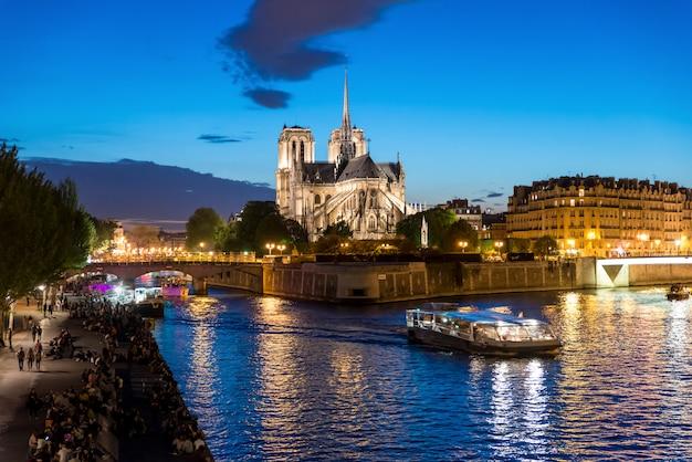 Notre dame de paris met cruiseschip op de rivier van de zegen bij nacht in parijs, frankrijk