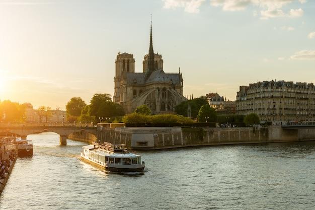 Notre dame de paris met cruiseschip op de rivier van de zegen in parijs, frankrijk
