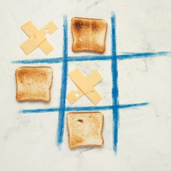 Noughts and crosses, choice, game competition of crosses from cheese and square toasted toast white stone