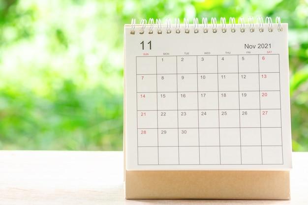 Novembermaand, kalenderbureau 2021 voor organisator tot planning en herinnering op houten tafel met groene natuurachtergrond.