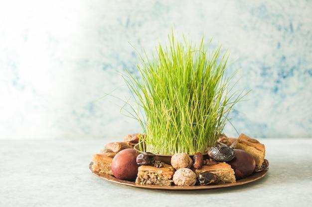 Novruz traditioneel dienblad met groen tarwegras semeni of sabzi, snoep en droog fruit pakhlava op witte achtergrond. lente-equinox, azerbeidzjan kopie ruimte