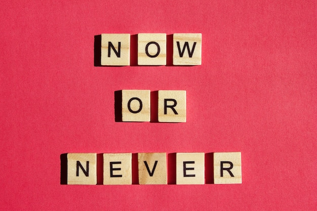 Nu of nooit - houten blokken met zwarte letters. oproep tot actie. motivatie voor iedereen.