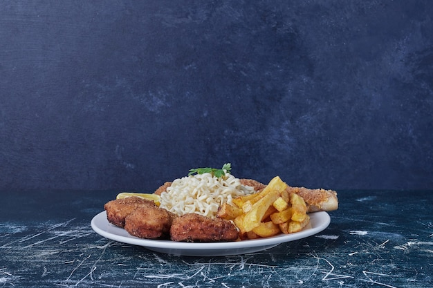 Nuggets met gebakken aardappelen en noedels.