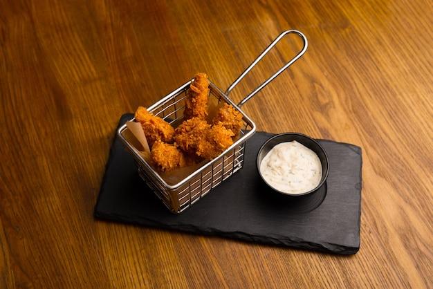 Nuggets van vingers in een metalen mand op een houten tafel.