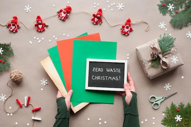 Nul afval kerstmis, plat lag, bovenaanzicht op ambachtelijke papier achtergrond - textiel poppen slinger, verpakte geschenken, handen houden schoolbord met tekst op stapel kleur papier. eco-vriendelijke eenvoudige groene kerst,