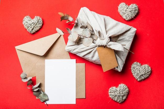 Nul afval valentijnsdagconcept op rood. eco-vriendelijke cadeauverpakking in furoshiki-stijl, ambachtelijke papieren envelop, lege wenskaart. bovenaanzicht of platliggend. kopieer ruimte voor ontwerp