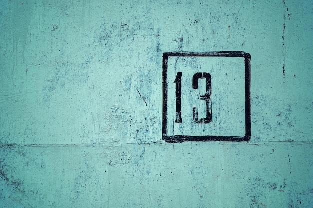 Nummer 13 is gestencild in zwart frame op groene betonnen muur, kopie ruimte