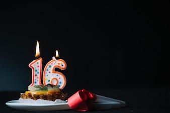 Nummer 16 verjaardag aangestoken kaars op de plak van scherpe en partijhoornventilator tegen zwarte achtergrond