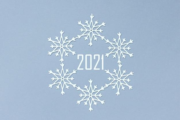 Nummer 2021 bevindt zich in een cirkel van sneeuwvlokken. witte decoratieve sneeuwvlokken op een grijze achtergrond.