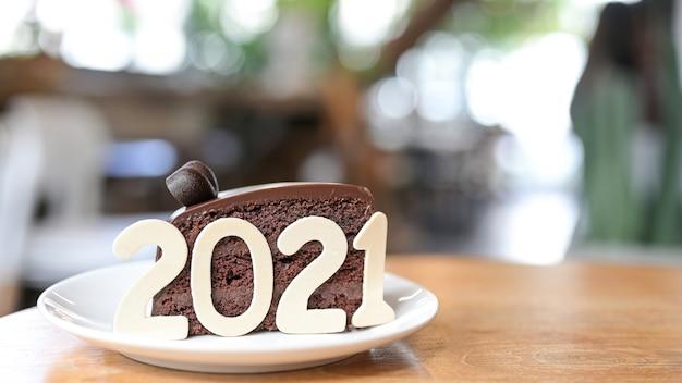 Nummer 2021 op een chocoladetaart op een houten tafel in het café.