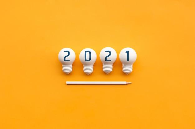 Nummer 2021 op gloeilampen en potlood, plat gelegd