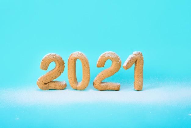 Nummer 2021 van gemberkoekjes wordt bestrooid met poedersuiker op een blauwe muur. feestelijke nieuwjaarsmuur, sjabloon voor wenskaarten. conceptueel ontwerp, ruimte voor tekst.