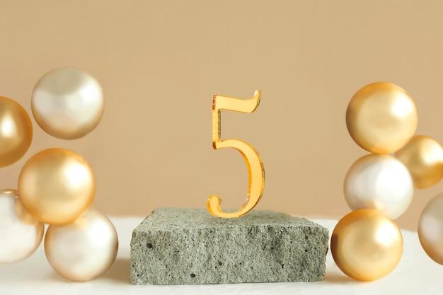 Nummer 5 op een betonnen podium en volumetrische gouden ballen op een beige achtergrond. ruimte kopiëren.