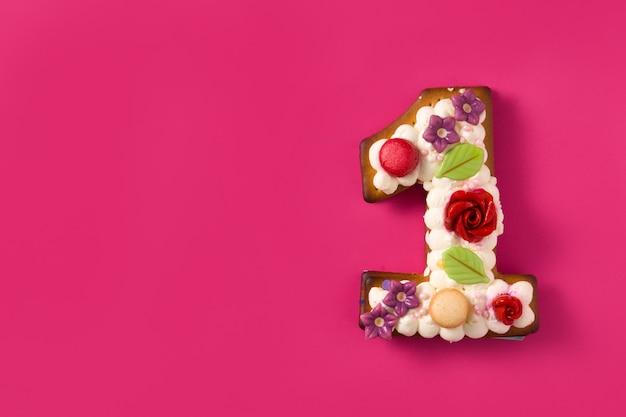 Nummer één cake versierd met bloemen en koekjes op roze oppervlak kopie ruimte