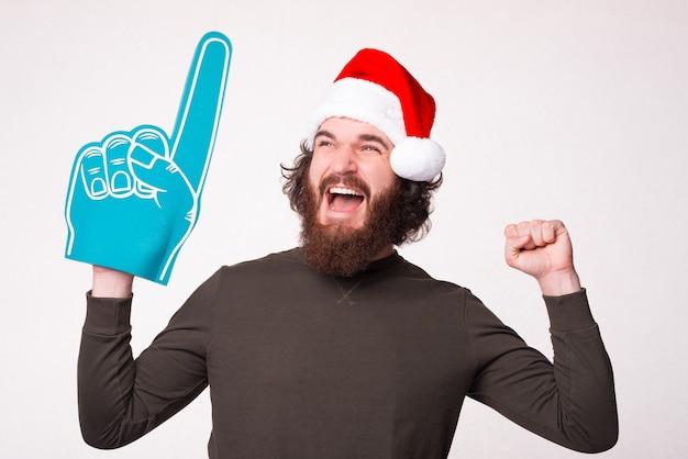 Nummer één fan van kerstvakantie. bebaarde man is opgewonden alsof hij iets heeft gewonnen.