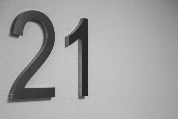 Nummer eenentwintig op lichte textuurmuur, die het jaar 2021 symboliseert.