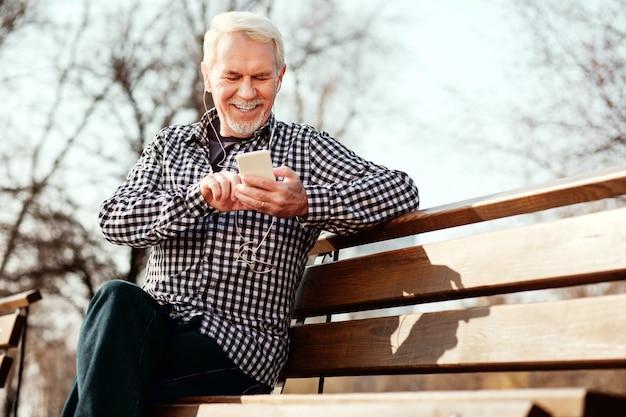 Nummer na nummer. lage hoek van vrolijke senior man naar beneden te staren en naar muziek te luisteren