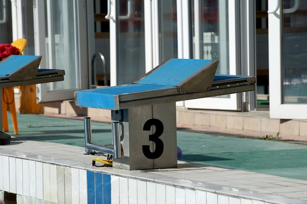 Nummer nachtkastje voor de sprong van de atleet naar het zwembad