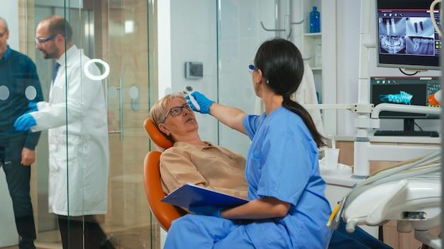 Nusre die de temperatuur van de oude vrouw meet voordat tandheelkundig onderzoek op de dokter wacht. tandartsassistente ondervraagt senior vrouw en maakt aantekeningen op klembord zittend op stomatologische stoel