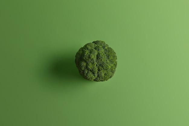 Nutritionele gezonde broccoli die van bovenaf op groene achtergrond wordt gefotografeerd. smakelijke groente kan rauw en gekookt gegeten worden. bron van vitamines. koken en eten concept. voedingsrijke koolsoort